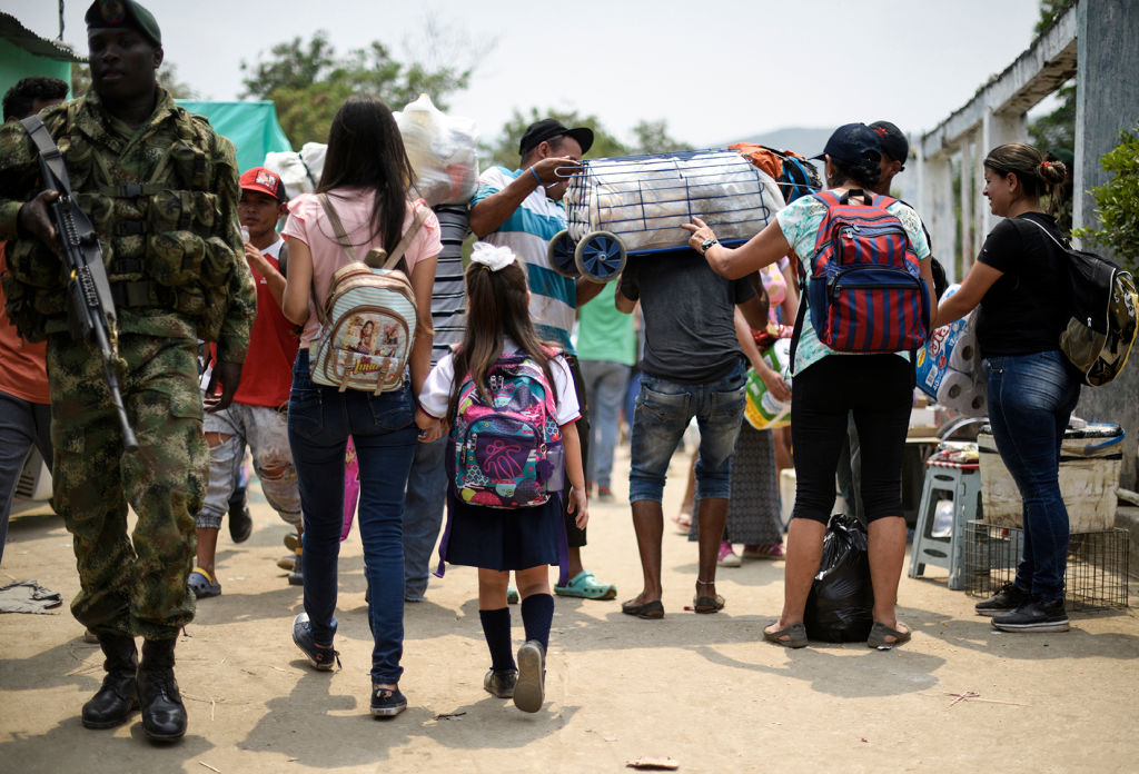 Venezuelan Leidy Navarro (L) walks with her daughter Valentina Caceres back to their home in Urena, Venezuela, after picking her up at school in Cucuta, Colombia, on March 6, 2019. - According to figures from the Secretary of Education of Cucuta, 9,174 Venezuelans study in schools in the capital of the department and, of them, about 3,000 cross the border every day. The crisis in Venezuela has also hit the educational system in the country, where dropout is high, there is a lack of teachers and schools buildings are suffering deterioration. (Photo by Juan Pablo BAYONA / AFP) (Photo credit should read JUAN PABLO BAYONA/AFP/Getty Images)