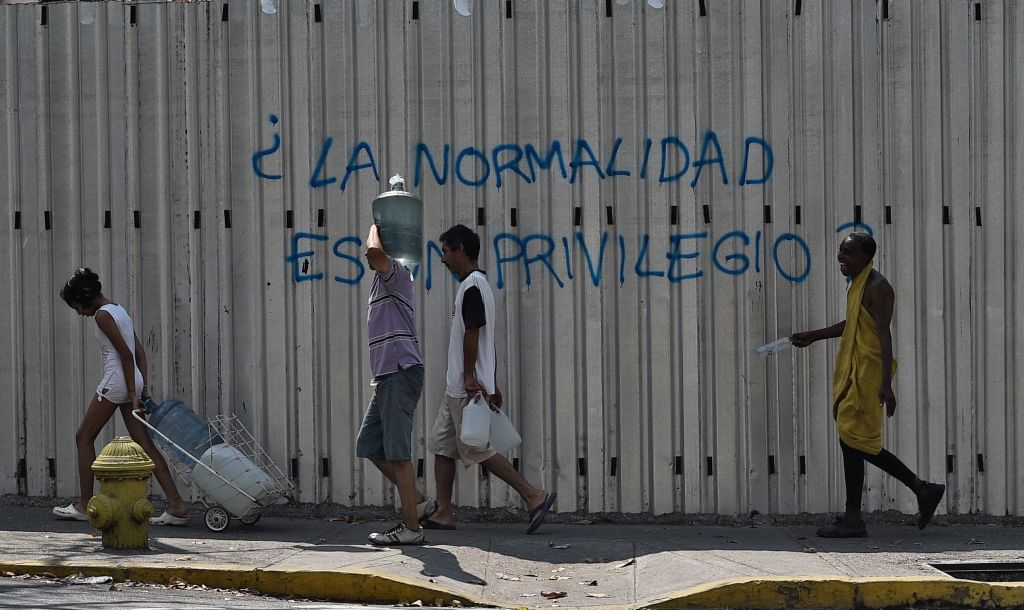 "People walk past a graffiti reading ""Is Normality a Privilege?"" during a new power outage in Venezuela, at Fuerzas Armadas Avenue in Caracas on March 31, 2019. - Living conditions are plummeting in the oil-producing Latin American nation, which is spiralling ever deeper into economic chaos during a protracted political crisis. (Photo by Federico PARRA / AFP) (Photo credit should read FEDERICO PARRA/AFP/Getty Images)"