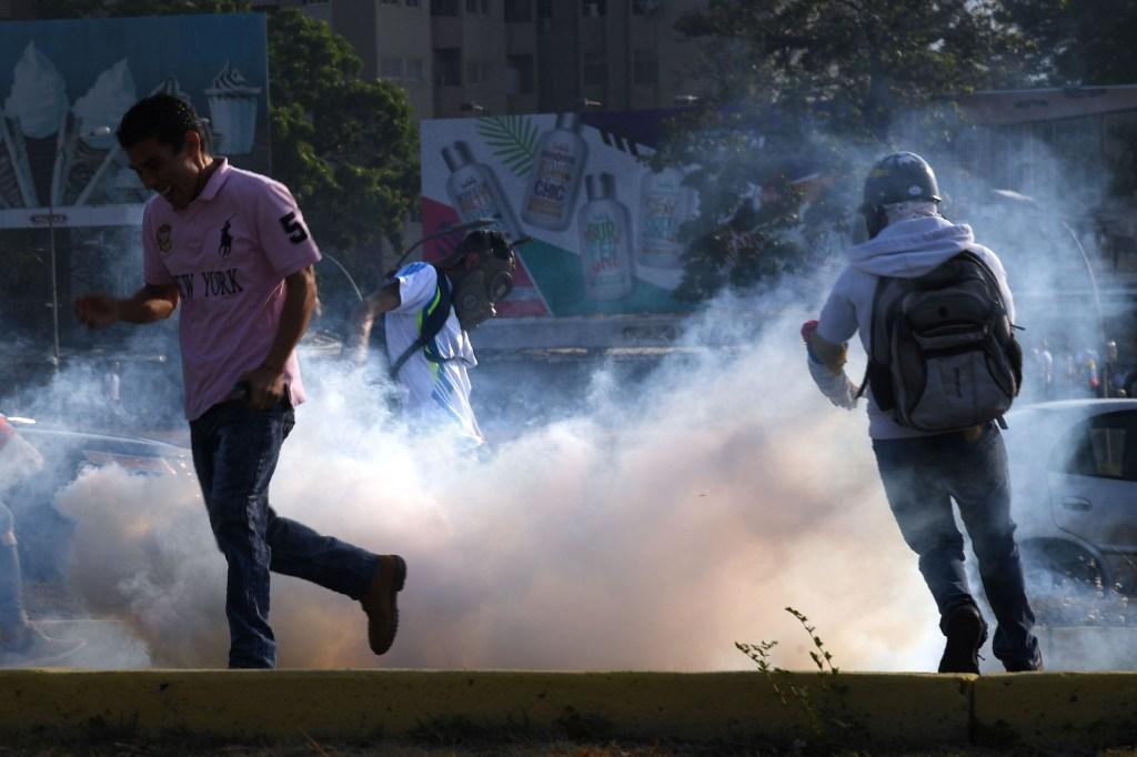 Un grupo de personas huye de los gases lacrimógenos durante los enfrentamientos con las fuerzas de seguridad en Caracas el 30 de abril de 2019. Crédito: YURI CORTEZ / AFP / Getty Images