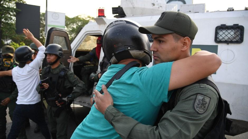Un hombre abraza a un miembro de las fuerzas de seguridad en Caracas el 30 de abril de 2019. Crédito: YURI CORTEZ / AFP / Getty Images.