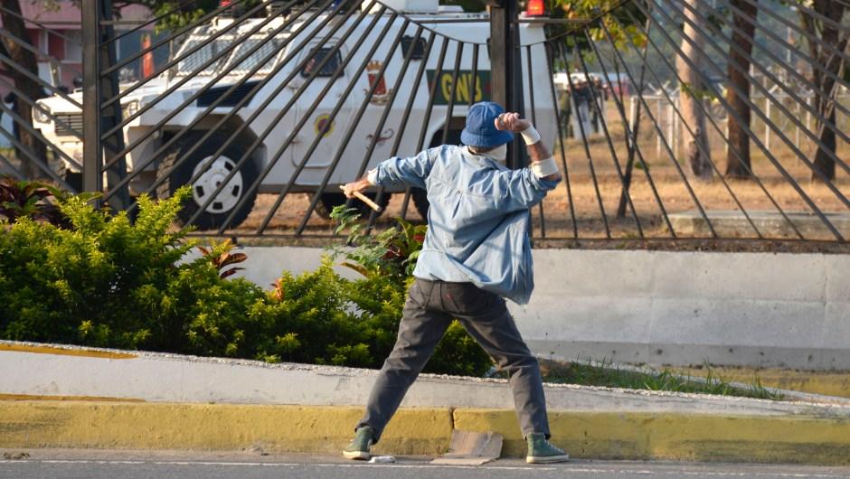 Un manifestante lanza una piedra a un vehículo de la Guardia Nacional el 30 de abril de 2019 en Caracas, Venezuela. Crédito: de Rafael Briceno / Getty Images