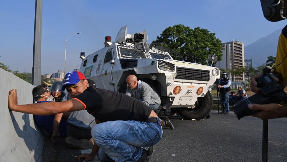 Venezolanos se protegen durante los enfrentamientos con las fuerzas de seguridad en Caracas el 30 de abril de 2019. Crédito: YURI CORTEZ / AFP / Getty Images