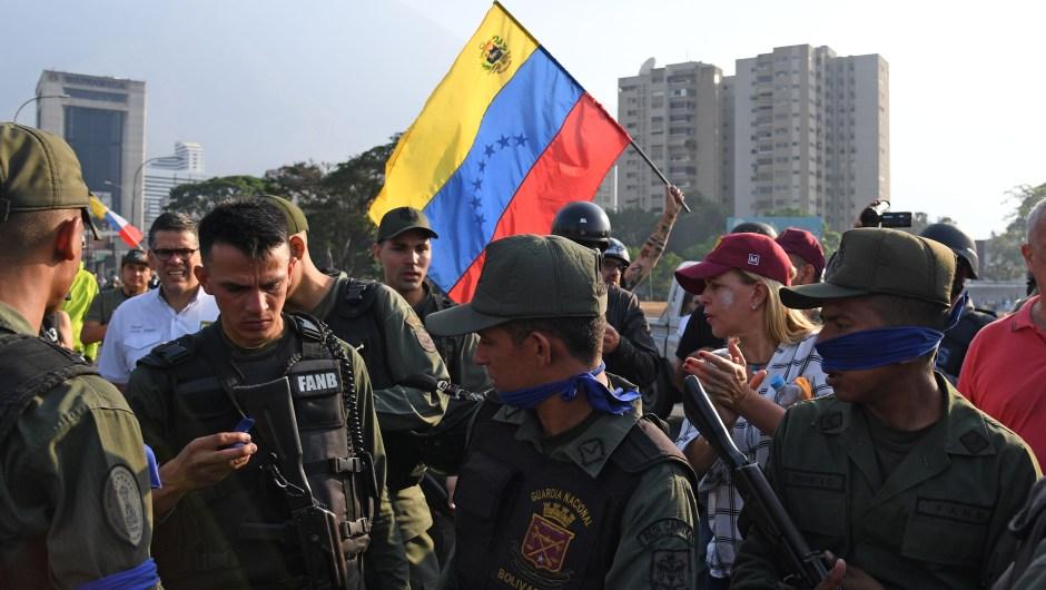 Un grupo de personas junto a miembros de las fuerzas de seguridad en Caracas el 30 de abril de 2019. Crédito: YURI CORTEZ / AFP / Getty Images