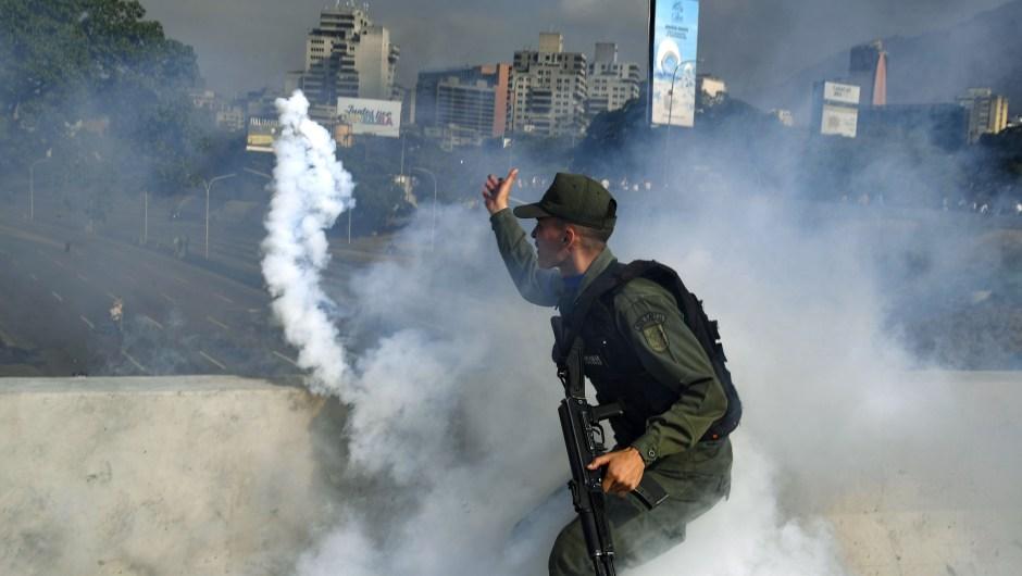 Un miembro de la Guardia Nacional Bolivariana que apoya a Juan Guaidó lanza un bote de gas lacrimógeno durante un enfrentamiento con guardias leales al gobierno del presidente Nicolás Maduro frente a la base militar de La Carlota en Caracas el 30 de abril de 2019. Crédito: YURI CORTEZ / AFP / Getty Images
