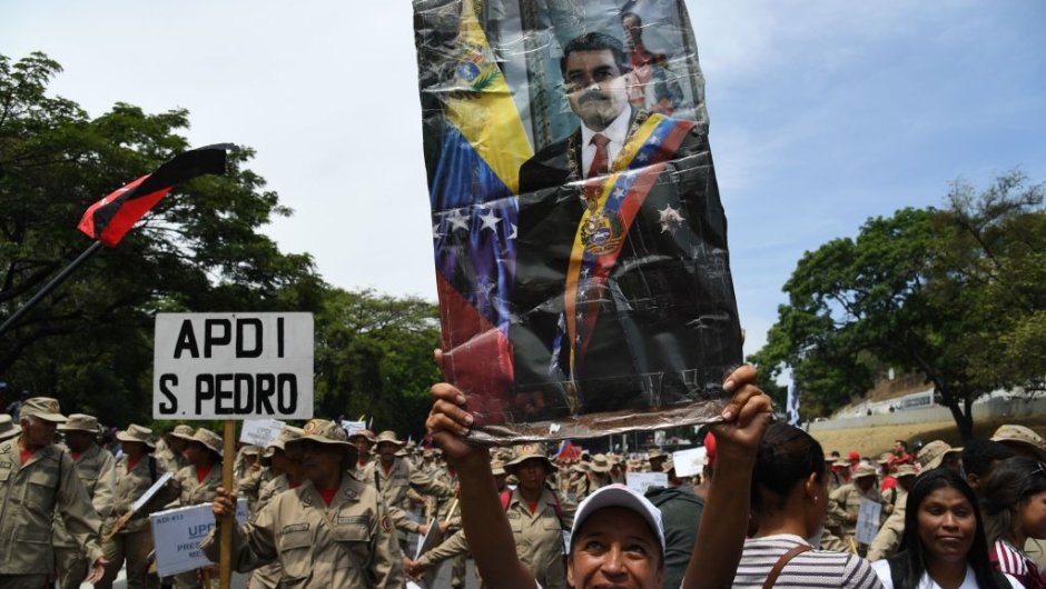 A supporter of Venezuelan President Nicolas Maduro displays a poster of Maduro during a rally on May Day in Caracas on May 1, 2019. - Pro- and anti-government rallies were due to take place in Venezuela, a day after violent clashes erupted in the capital following opposition leader Juan Guido's call on the military to rise up against Maduro, who claimed the insurrection had failed. (Photo by Yuri CORTEZ / AFP) (Photo credit should read YURI CORTEZ/AFP/Getty Images)