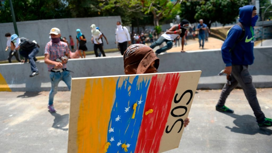 Anti-government protesters carry a shield and Molotov cocktails as thousands of other opposition demonstrators march in Caracas to commemorate May Day on May 1, 2019 after a day of violent clashes on the streets of the capital spurred by Venezuela's opposition leader Juan Guaido's call on the military to rise up against President Nicolas Maduro. - Guaido called for a massive May Day protest to increase the pressure on President Maduro. (Photo by Matias Delacroix / AFP) (Photo credit should read MATIAS DELACROIX/AFP/Getty Images)