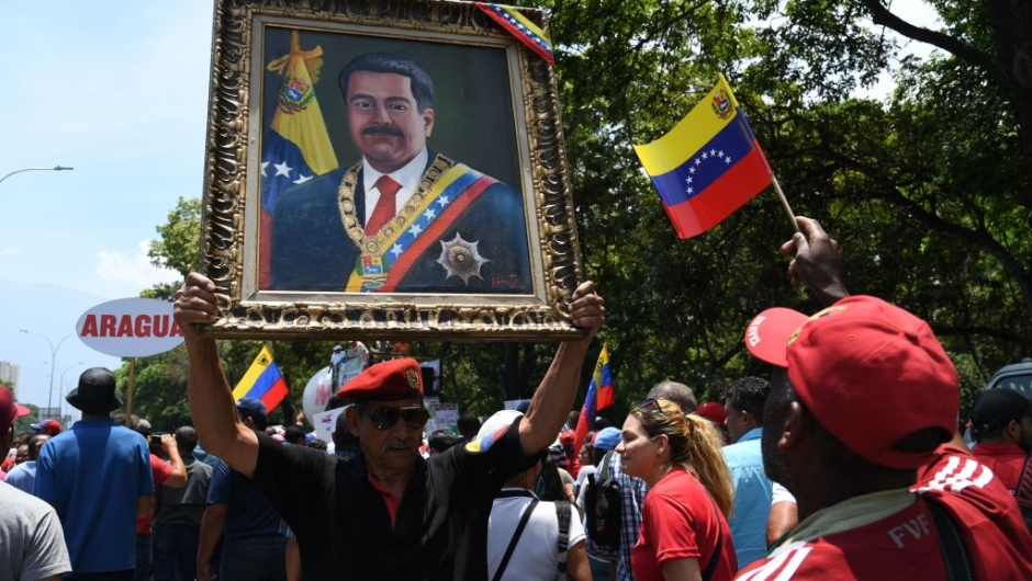 A supporter of President Nicolas Maduro display a painting of the Venezuelan leader during a rally on May Day in Caracas on May 1, 2019. - Pro- and anti-government rallies were due to take place in Venezuela, a day after violent clashes erupted in the capital following opposition leader Juan Guido's call on the military to rise up against Maduro, who claimed the insurrection had failed. (Photo by Yuri CORTEZ / AFP) (Photo credit should read YURI CORTEZ/AFP/Getty Images)