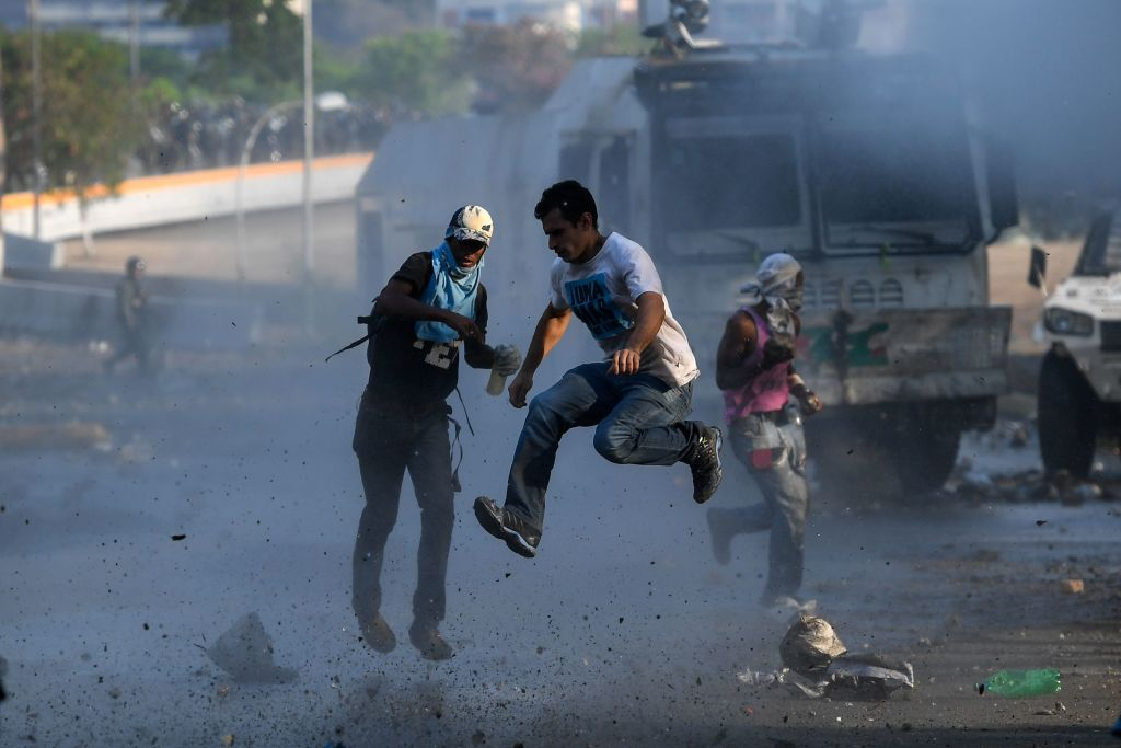 TOPSHOT - Anti-government protesters clash with security forces in Caracas during the commemoration of May Day on May 1, 2019. - Opposition supporters demonstrated for a second consecutive day in support of their country's self-proclaimed leader Juan Guaido as he bids to overthrow President Nicolas Maduro. Maduro and his government have vowed to put down what they see as an attempted coup by the US-backed opposition leader. (Photo by Federico PARRA / AFP) (Photo credit should read FEDERICO PARRA/AFP/Getty Images)