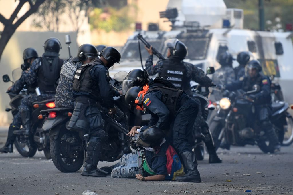 TOPSHOT - An anti-government protester is detained by security forces during clashes with security forces in Caracas on the commemoration of May Day on May 1, 2019, after a day of violent clashes on the streets of the capital spurred by Venezuela's opposition leader Juan Guaido's call on the military to rise up against President Nicolas Maduro. - Guaido called for a massive May Day protest to increase the pressure on Venezuelan President Nicolas Maduro. (Photo by Federico PARRA / AFP) (Photo credit should read FEDERICO PARRA/AFP/Getty Images)