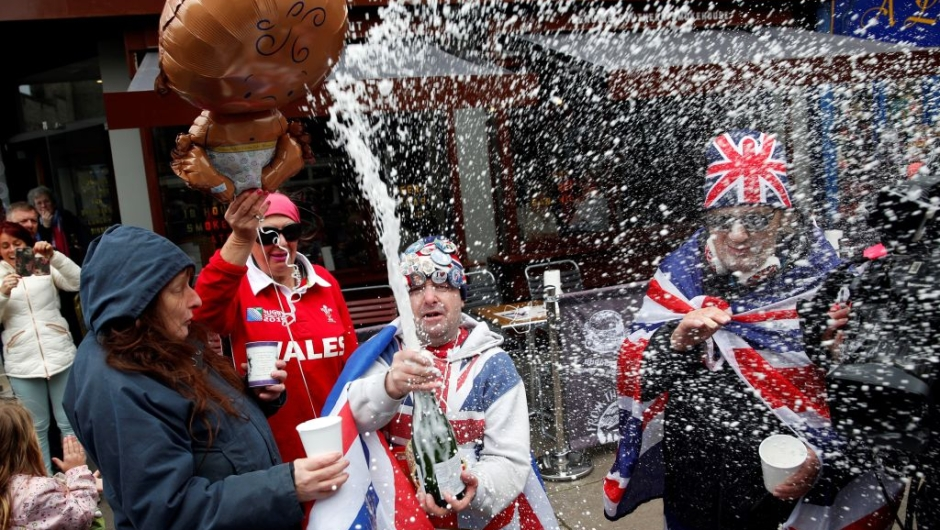"""Royal super fans John Loughery (C) pops the cork on a bottle of champagne, as they stand near Windsor Castle in Windsor, west of London on May 6, 2019, following the announcement that Britain's Meghan, Duchess of Sussex has given birth to a son. - Meghan Markle, the Duchess of Sussex, gave birth on Monday to a """"very healthy"""" boy, Prince Harry announced. """"We're delighted to announce that Meghan and myself had a baby boy early this morning -- a very healthy boy,"""" a beaming Prince Harry said. (Photo by ADRIAN DENNIS / AFP) (Photo credit should read ADRIAN DENNIS/AFP/Getty Images)"""