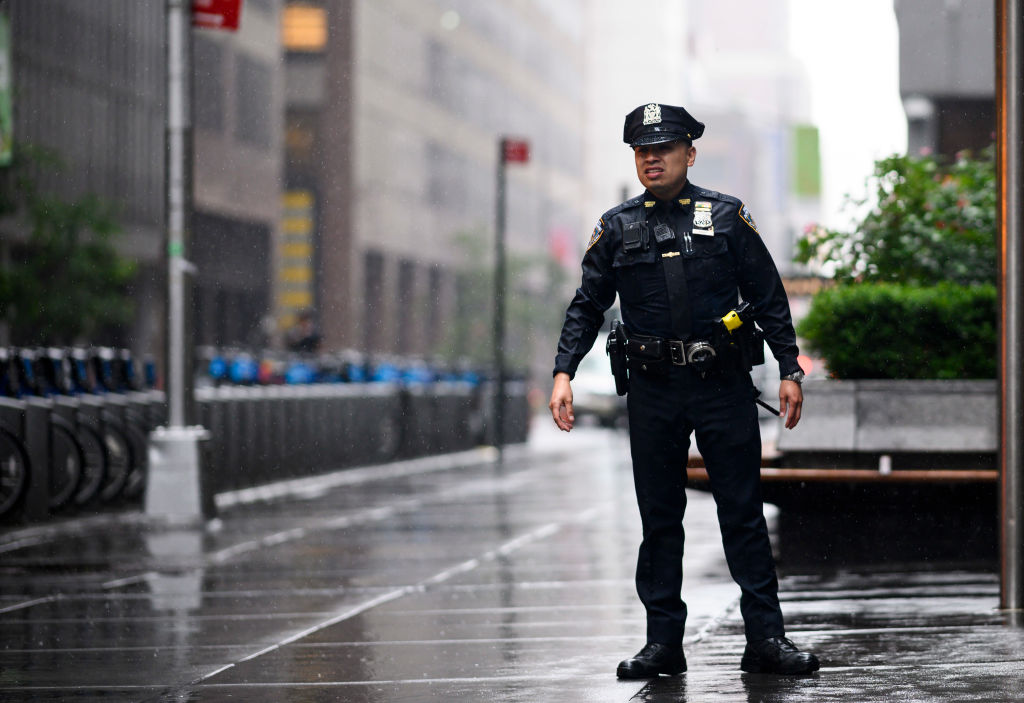 "A policeman looks down a street after a helicopter crash-landed on top of a building in midtown Manhattan in New York on June 10, 2019. - Speaking at the scene New York Governor Andrew Cuomo told reporters there had been ""casualties"" on board the helicopter, but that no one in the building had been hurt. (Photo by Johannes EISELE / AFP) (Photo credit should read JOHANNES EISELE/AFP/Getty Images)"