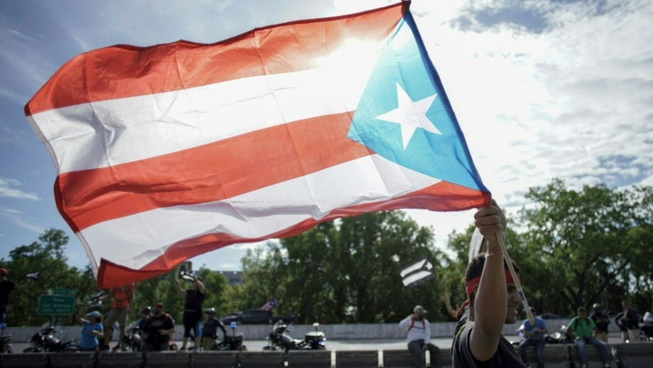 A protester waves the Puerto Rican flag in San Juan, Puerto Rico, July 22, 2019 on day 9th of continuous protests demanding the resignation of Governor Ricardo Rosselló. - Protests erupted last week after the leak of hundreds of pages of text chats on the encrypted messaging app Telegram in which Rossello and 11 other male administration members criticize officials, politicians and journalists. In one exchange, chief financial officer Christian Sobrino makes homophobic references to Latin superstar Ricky Martin. In another, a mocking comment is made about bodies piled up in the morgue after Hurricane Maria, which left nearly 3,000 dead. (Photo by eric rojas / AFP) (Photo credit should read ERIC ROJAS/AFP/Getty Images)