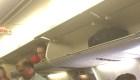 Auxiliar de vuelo trepa en compartimento de maletas