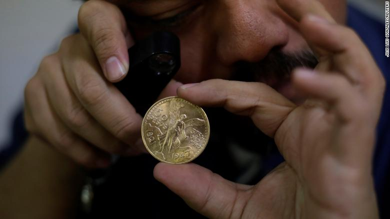 The owner of an antiques shop checks a Mexican gold coin, or Centenario, in Ciudad Juarez, Mexico November 10, 2017. Picture taken November 10, 2017. REUTERS/Jose Luis Gonzalez