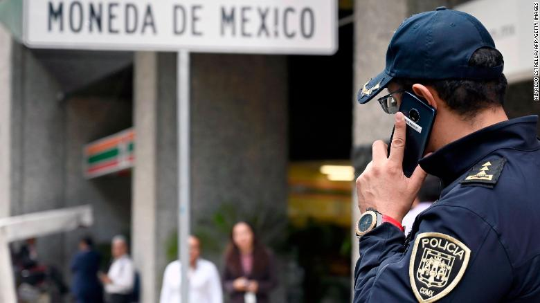"A policeman speaks on his mobile phone outside Mexico's Casa de Moneda, in Mexico City on August 6, 2019, which was robbed earlier today and the assailants took a swag of approximately two and a half million dollars in gold coins called ""Centenarios"". (Photo by ALFREDO ESTRELLA / AFP) (Photo credit should read ALFREDO ESTRELLA/AFP/Getty Images)"