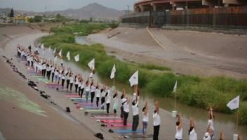 Clase masiva de yoga junto al río Bravo para derribar muros