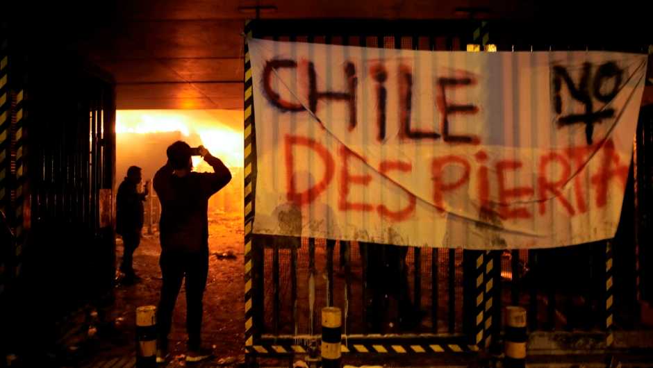 "TOPSHOT - People take pictures of Macul Metro station set on fire by protesters alongside a sign that reads ""Chile doesn't wake up"" during a mass fare-dodging protest in Santiago, on October 19, 2019. - The entire Santiago Metro, which mobilizes about three million passengers per day, stopped operating on Friday afternoon following attacks in rejection of the rate hike, the company said. The chaos beat Santiago this Friday with confrontations, fires and attacks on the metropolitan railway, in protest of the increase in fares that forced the closure of all Metro stations. (Photo by JAVIER TORRES / AFP) (Photo by JAVIER TORRES/AFP via Getty Images)"