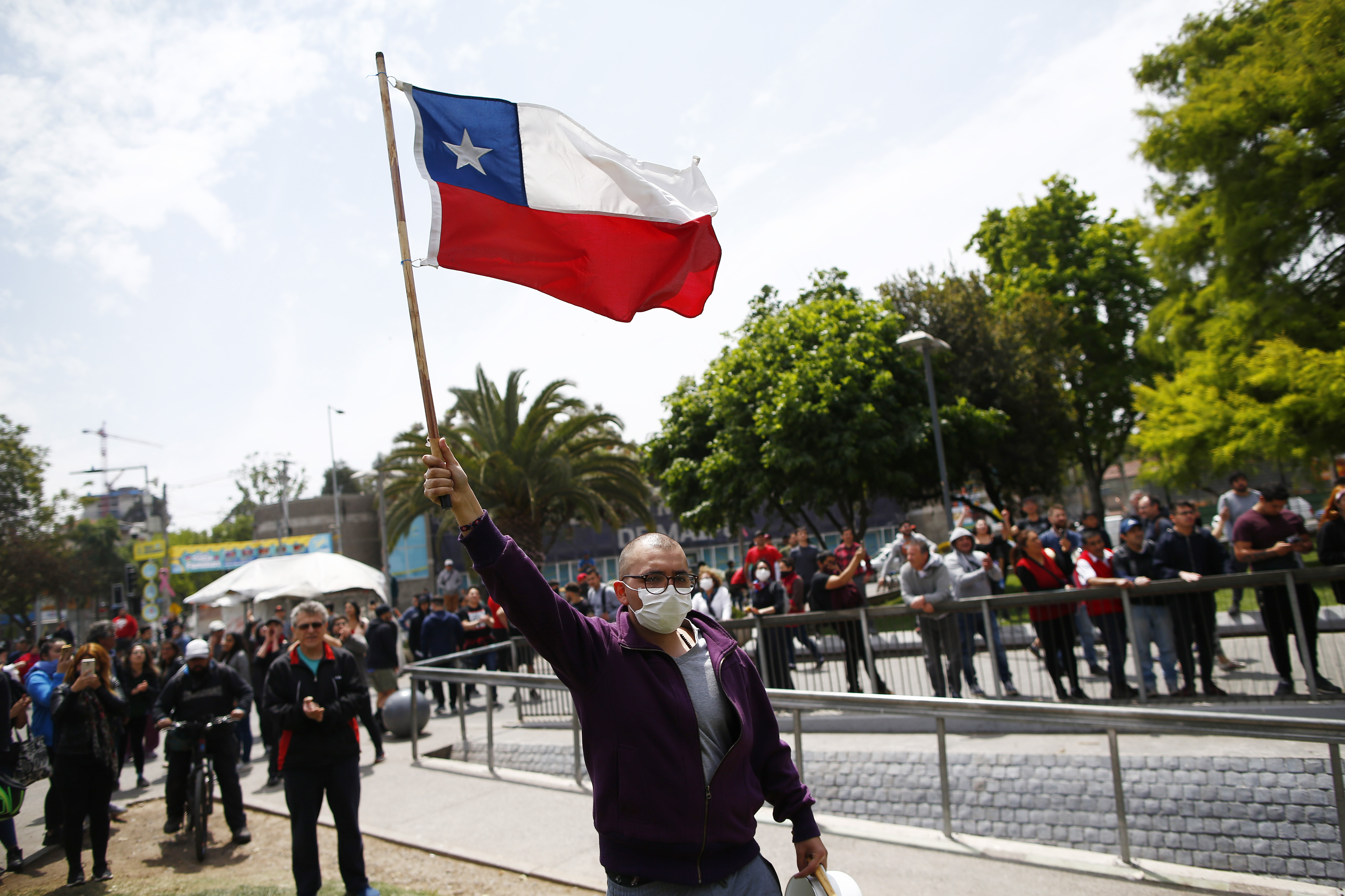 TOPSHOT - A demonstrator waves a chilean flag outside of the Plaza Maipu metro station during clashes between protesters and the riot police at Plaza de Maipu in Santiago, on October 19, 2019. - Chile's president declared a state of emergency in Santiago Friday night and gave the military responsibility for security after a day of violent protests over an increase in the price of metro tickets. (Photo by Pablo VERA / AFP) (Photo by PABLO VERA/AFP via Getty Images)