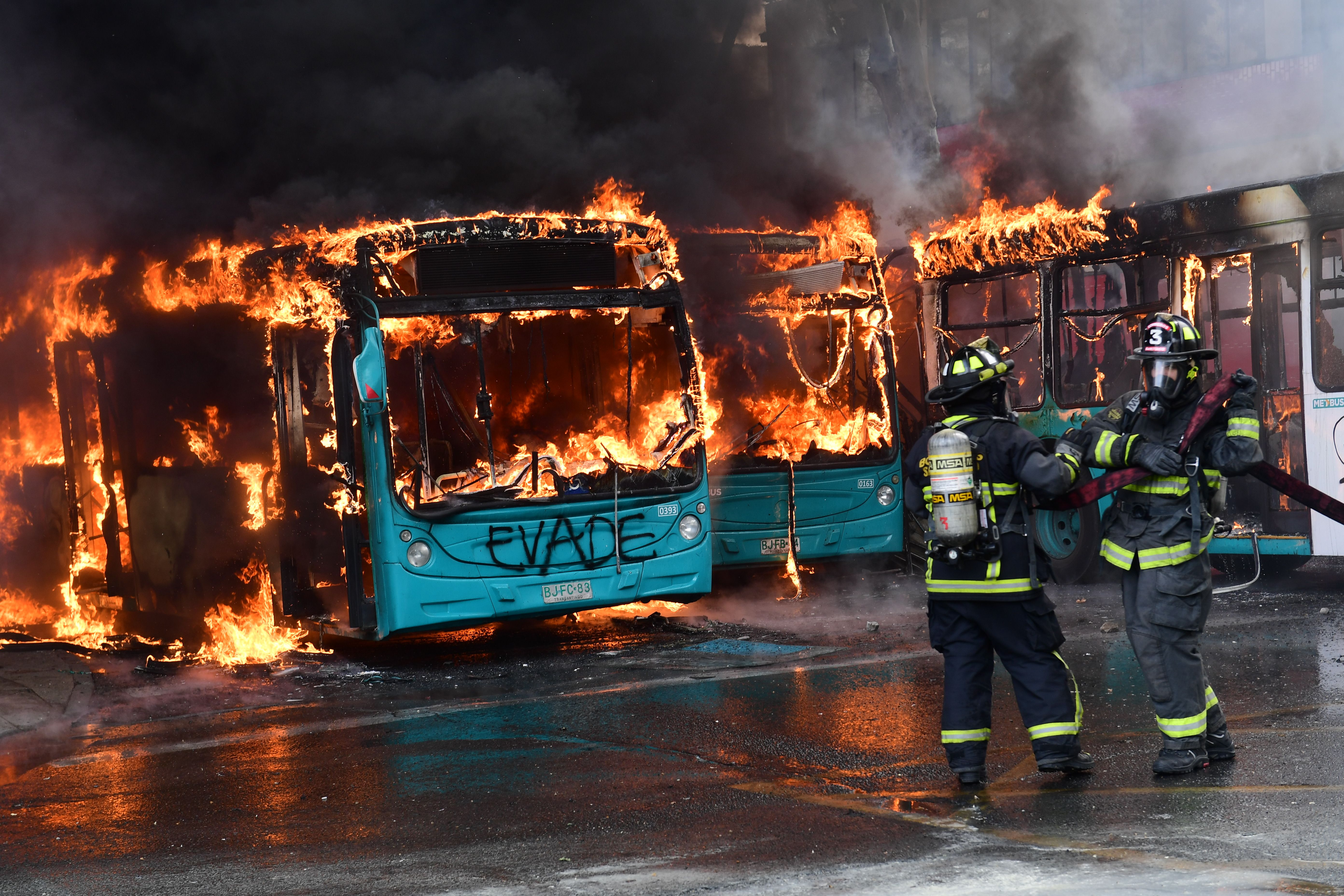 TOPSHOT - Chilean firefighters extinguish a burning bus during clashes between protesters and the riot police in Santiago, on October 19, 2019. - Chile's president declared a state of emergency in Santiago Friday night and gave the military responsibility for security after a day of violent protests over an increase in the price of metro tickets. (Photo by Martin BERNETTI / AFP) (Photo by MARTIN BERNETTI/AFP via Getty Images)