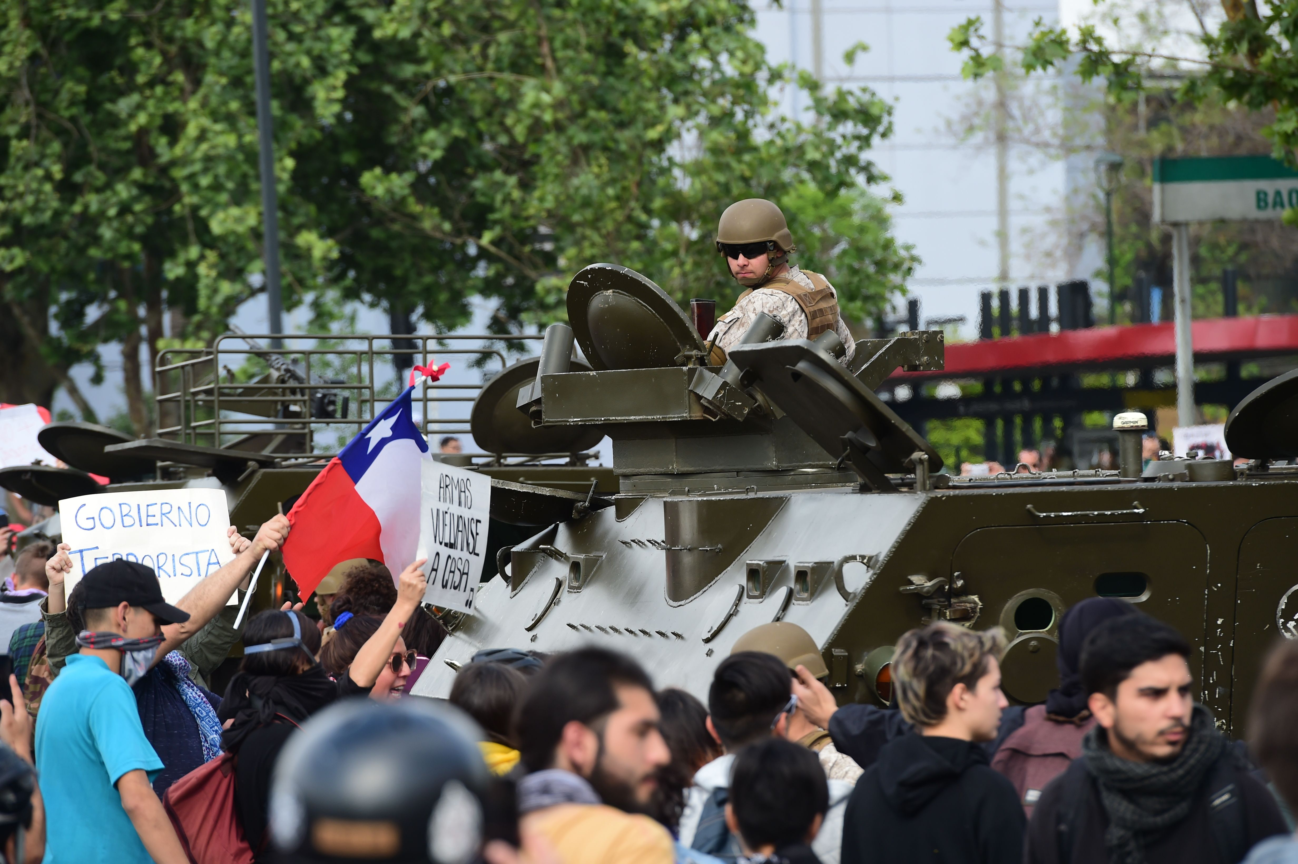 A soldier in a tank is surrounded by demonstrators in Santiago, on October 19, 2019. - Chile's president declared a state of emergency in Santiago Friday night and gave the military responsibility for security after a day of violent protests over an increase in the price of metro tickets. (Photo by Martin BERNETTI / AFP) (Photo by MARTIN BERNETTI/AFP via Getty Images)