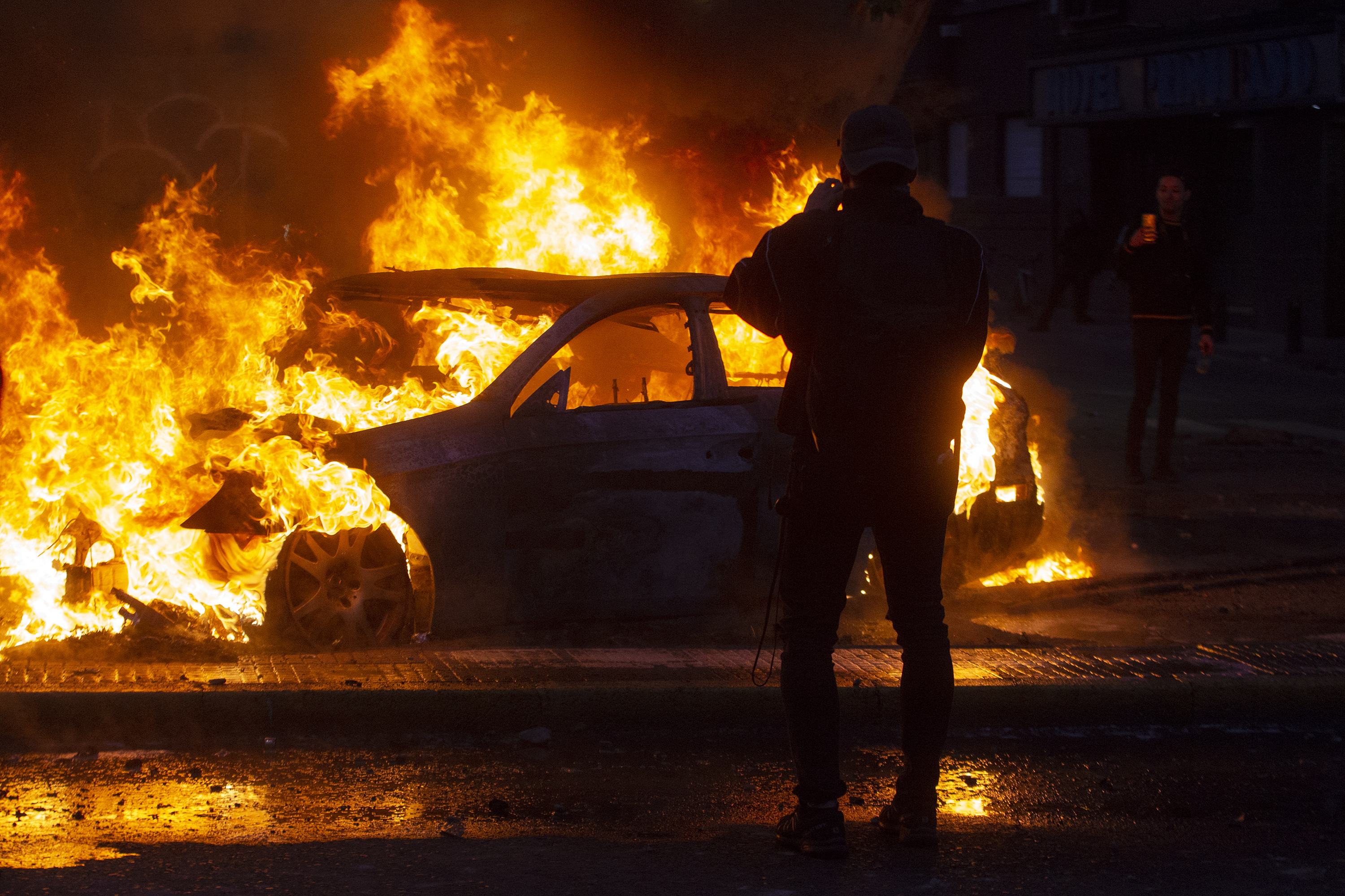 TOPSHOT - Men take pictures of a burning car during violent protests in Santiago, on October 19, 2019. - Chile's president declared a state of emergency in Santiago Friday night and gave the military responsibility for security after a day of violent protests over an increase in the price of metro tickets. (Photo by CLAUDIO REYES / AFP) (Photo by CLAUDIO REYES/AFP via Getty Images)