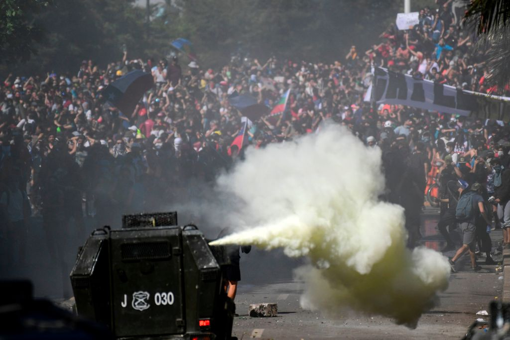 TOPSHOT - Demonstrators clash with riot police on a fifth straight day of street violence which erupted over a now suspended hike in metro ticket prices, in Santiago, on October 22, 2019. - President Sebastian Pinera convened a meeting with leaders of Chile's political parties on Tuesday in the hope of finding a way to end street violence that has claimed 15 lives, as anti-government campaigners threatened new protests. (Photo by Martin BERNETTI / AFP) (Photo by MARTIN BERNETTI/AFP via Getty Images)