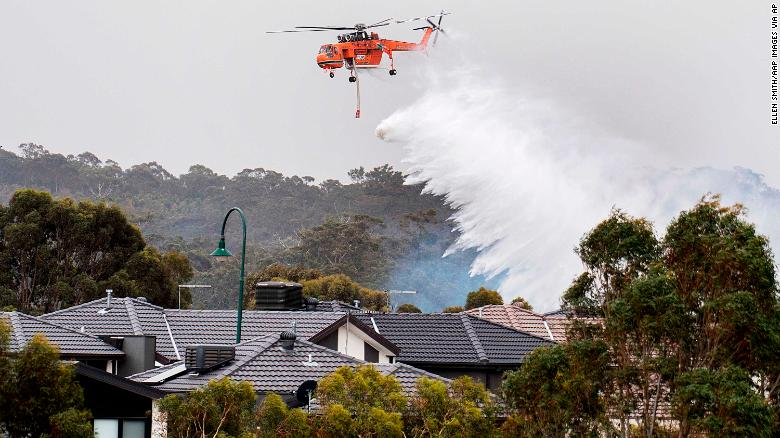 A skycrane drops water on a bushfire in scrub behind houses in Bundoora, Melbourne, Monday, Dec. 30, 2019. New Year???s Eve fireworks in Australia???s capital and other cities have been canceled as the wildfire danger worsens in oppressive summer heat, and pressure was building for Sydney???s iconic celebrations to be similarly scrapped.(Ellen Smith/AAP Images via AP)