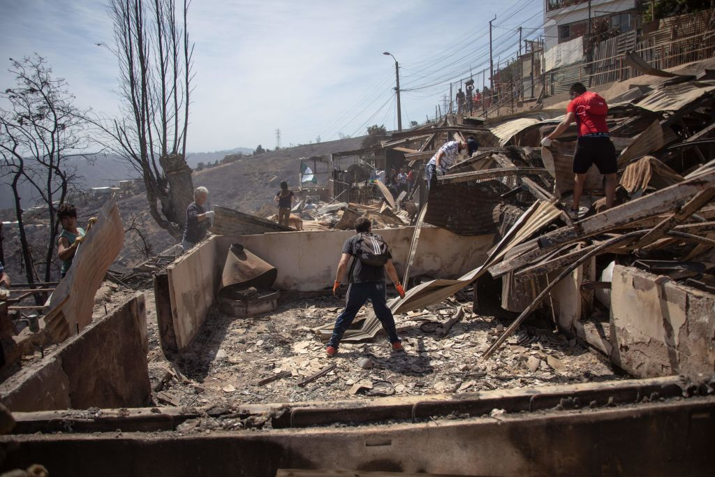 TOPSHOT - Locals search for personal belongings after a forest fire at the Rocuant hill in Valparaiso, Chile, on December 25, 2019. - Around 200 houses were affected by a forest fire Tuesday in Valparaiso, where a red alert was declared. (Photo by Pablo ROJAS MARIADAGA / AFP) (Photo by PABLO ROJAS MARIADAGA/AFP via Getty Images)