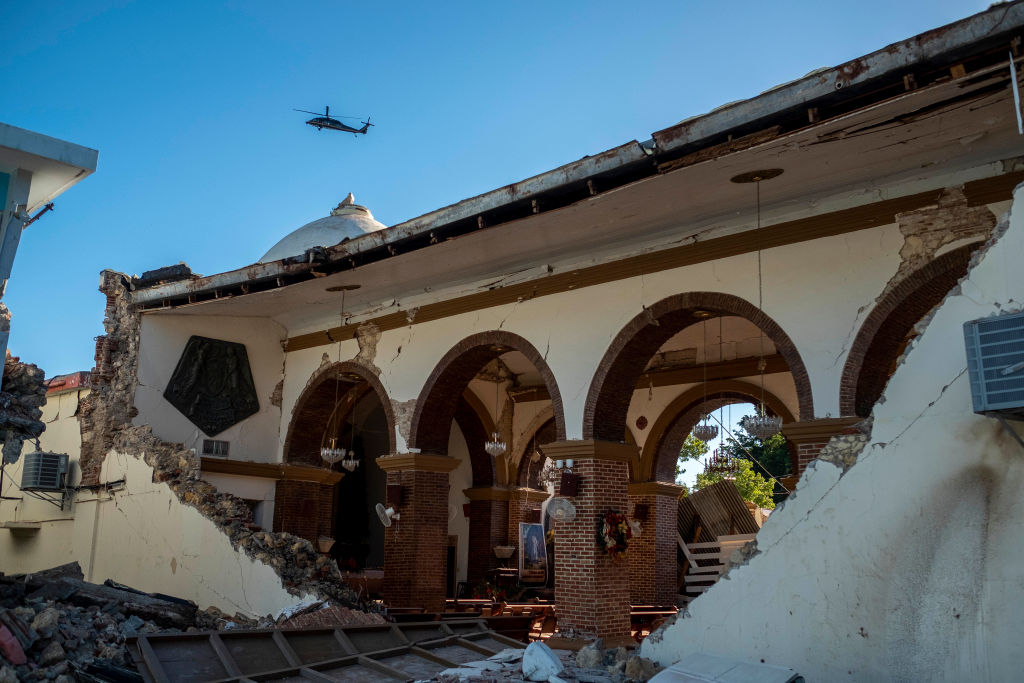 A helicopter flies over the Inmaculada Concepcion church, built in 1841, seen partially collapsed after an  earthquake hit the island in Guayanilla, Puerto Rico on January 7, 2020. - A strong earthquake struck south of Puerto Rico early January 7, 2020 followed by major aftershocks, the US Geological Survey said, the latest in a series of tremors that have shaken the island since December 28. The shallow 6.4 magnitude quake struck five miles (eight kilometers) south of the community of Indios, the USGS said, revising down its initial reading of 6.6. (Photo by Ricardo ARDUENGO / AFP) (Photo by RICARDO ARDUENGO/AFP via Getty Images)