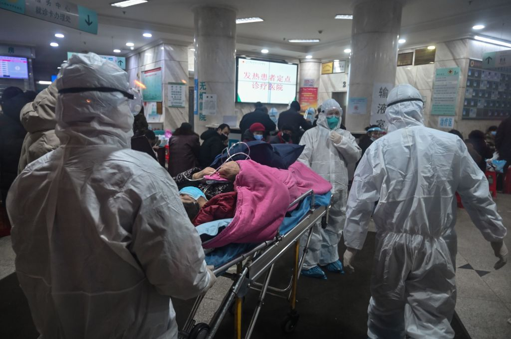 TOPSHOT - In this photo taken on January 25, 2020, medical staff wearing protective clothing to protect against a previously unknown coronavirus arrive with a patient at the Wuhan Red Cross Hospital in Wuhan. - The number of confirmed deaths from a viral outbreak in China has risen to 54, with authorities in hard-hit Hubei province on January 26 reporting 13 more fatalities and 323 new cases. (Photo by Hector RETAMAL / AFP) (Photo by HECTOR RETAMAL/AFP via Getty Images)