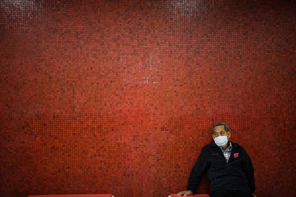 TOPSHOT - A man wearing a face mask sits on a bench as he waits on a platform for a MTR underground metro train during a Lunar New Year of the Rat public holiday in Hong Kong on January 27, 2020, as a preventative measure following a coronavirus outbreak which began in the Chinese city of Wuhan. (Photo by Anthony WALLACE / AFP) (Photo by ANTHONY WALLACE/AFP via Getty Images)