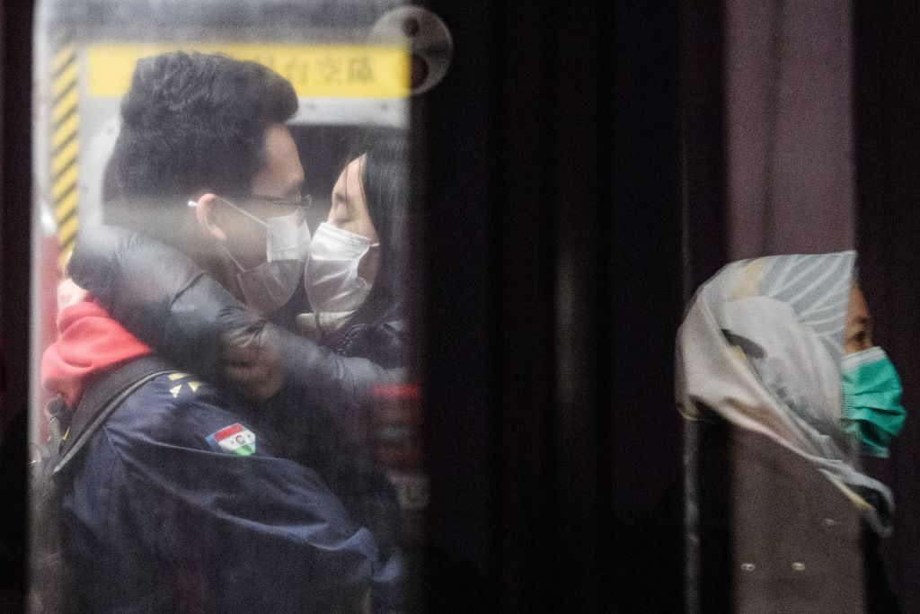 TOPSHOT - A couple wearing face masks kiss on an underground metro train as another passenger (R) is reflected on a platform glass door during a Lunar New Year of the Rat public holiday in Hong Kong on January 27, 2020, as a preventative measure following a coronavirus outbreak which began in the Chinese city of Wuhan. (Photo by Anthony WALLACE / AFP) (Photo by ANTHONY WALLACE/AFP via Getty Images)