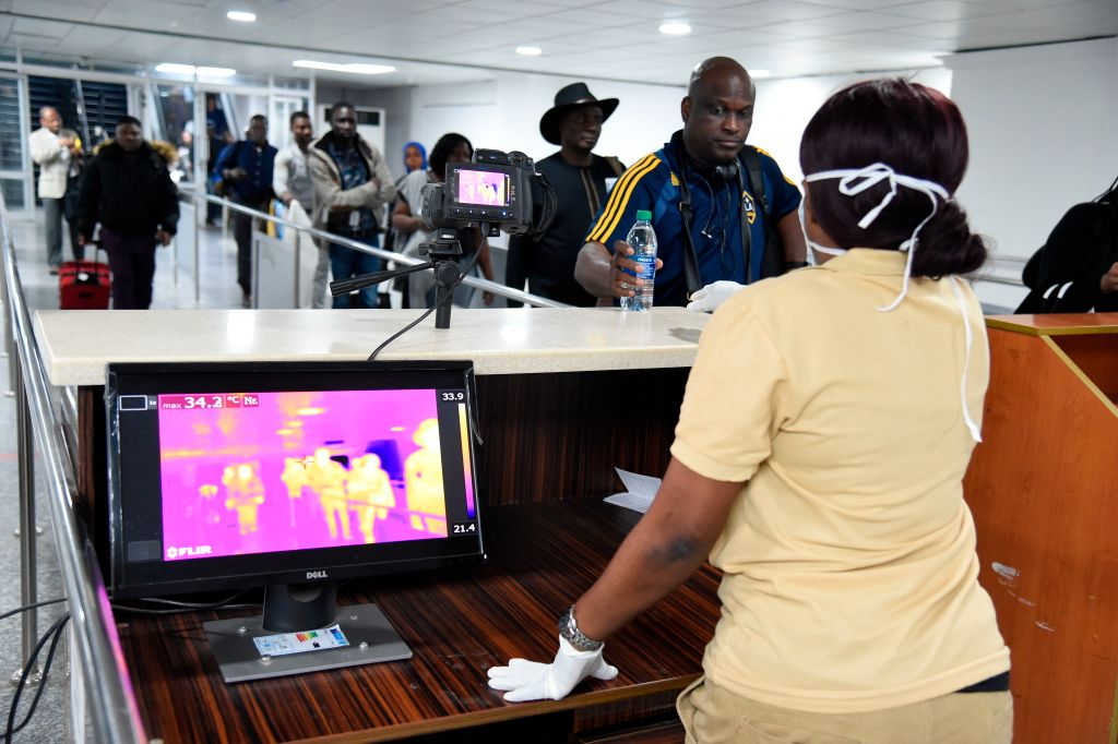 TOPSHOT - A Port Health Service staff member stands next to a thermal scanner as passengers arrive at the Murtala Mohammed International Airport in Lagos, Nigeria, on January 27, 2019. - The Port Health Services Unit of the Federal Ministry of Health in Nigeria has been placed on alert and has heightened screening measures at the points of entry to screen travellers arriving the country. The Nigeria Immigration Service and Port Health Services have expressed fears over the outbreak of Coronavirus in China. (Photo by PIUS UTOMI EKPEI / AFP) (Photo by PIUS UTOMI EKPEI/AFP via Getty Images)