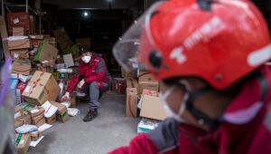 WUHAN, CHINA - JANUARY 29: (CHINA OUT) A courier organizes packages in an Express station on January 29, 2020 in Hubei Province, Wuhan, China. Due to a transit shut down and lack of supplies, couriers have became the city's suppliers. The 2019 coronavirus (2019-nCoV), which originated in Wuhan, China, has infected 6078 people and killed at least 132, mostly in China. (Photo by Getty Images)