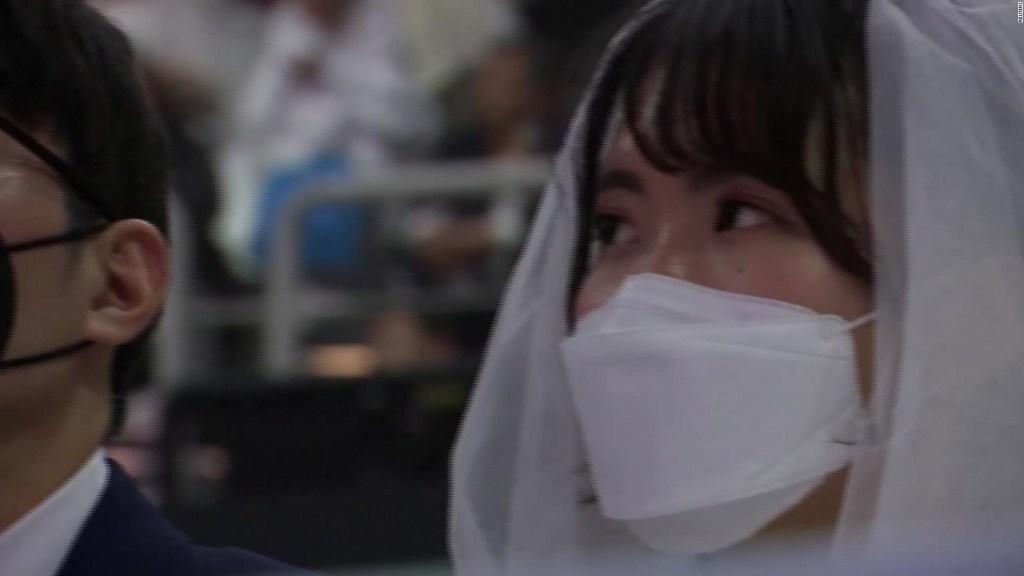 Miles de parejas usan mascarilla en boda masiva