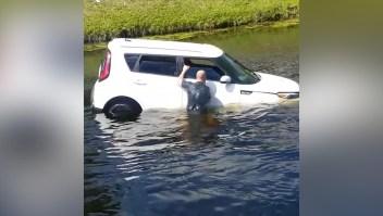 Transeúntes rescatan a una mujer de un auto que se hunde