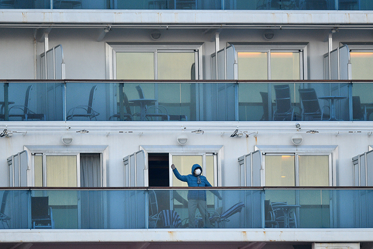 A passenger is seen on a balconies of the Diamond Princess cruise ship, with around 3,600 people quarantined onboard due to fears of the new coronavirus, at the Daikaku Pier Cruise Terminal in Yokohama port on February 13, 2020. - At least 218 people on board a cruise ship quarantined off Japan have tested positive for the novel COVID-19 coronavirus, authorities said February 13 as they announced plans to move some elderly passengers off the ship. (Photo by Kazuhiro NOGI / AFP) (Photo by KAZUHIRO NOGI/AFP via Getty Images)