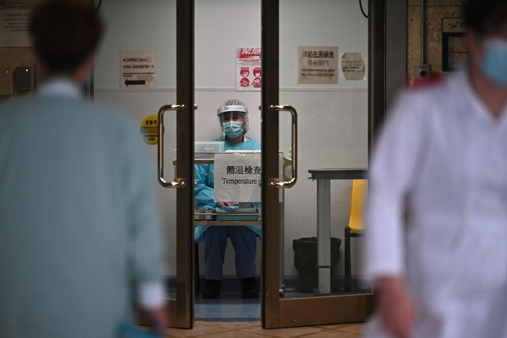 TOPSHOT - A medical worker wearing protective gear (C) waits to take the temperature of people in an entrance of Princess Margaret Hospital in Hong Kong on February 4, 2020. - Hong Kong on February 4 become the second place outside of the Chinese mainland to report the death of a patient being treated for a new coronavirus that has so far claimed more than 400 lives. (Photo by Anthony WALLACE / AFP) (Photo by ANTHONY WALLACE/AFP via Getty Images)