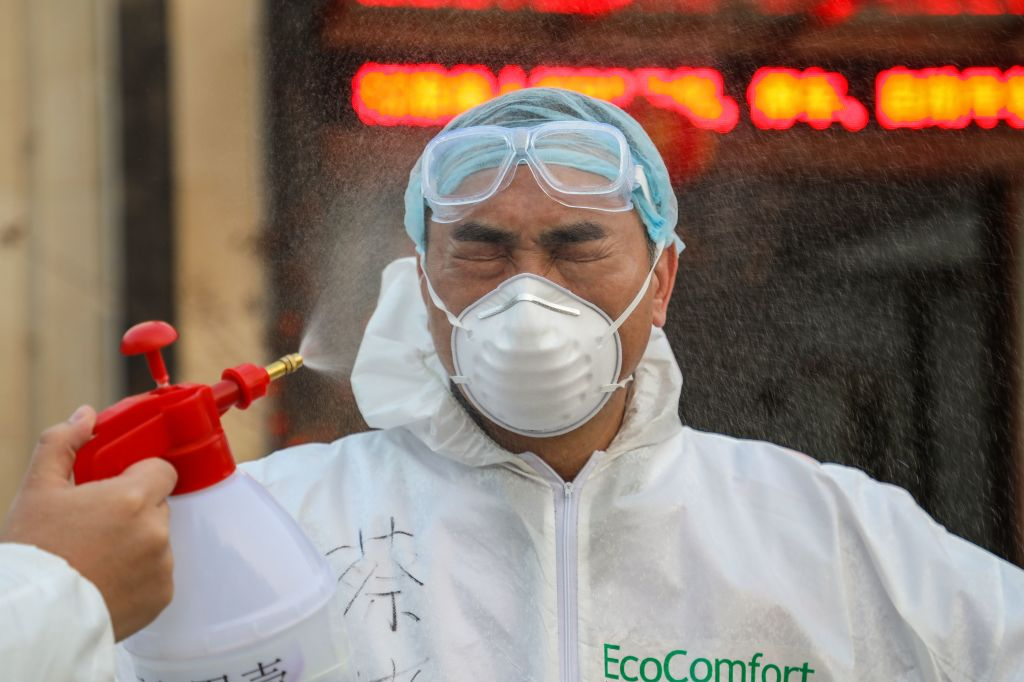 This photo taken on February 3, 2020 shows a doctor being disinfected by his colleague at a quarantine zone in Wuhan, the epicentre of the new coronavirus outbreak, in China's central Hubei province. - The number of total infections in China's coronavirus outbreak has passed 20,400 nationwide with 3,235 new cases confirmed, the National Health Commission said on February 4. (Photo by STR / AFP) / China OUT (Photo by STR/AFP via Getty Images)
