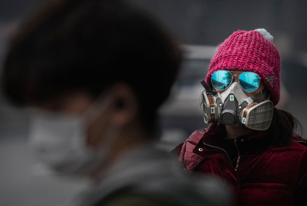 BEIJING, CHINA - FEBRUARY 13: A Chinese woman wears a protective mask as she waits for a bus at a usually busy stop on February 13, 2020 in Beijing, China. The number of cases of the deadly new coronavirus COVID-19 rose to more than 52000 in mainland China Thursday, in what the World Health Organization (WHO) has declared a global public health emergency. China continued to lock down the city of Wuhan in an effort to contain the spread of the pneumonia-like disease which medicals experts have confirmed can be passed from human to human. In an unprecedented move, Chinese authorities have maintained and in some cases tightened the travel restrictions on the city which is the epicentre of the virus and also in municipalities in other parts of the country affecting tens of millions of people. The number of those who have died from the virus in China climbed to over 1300 on Thursday, mostly in Hubei province, and cases have been reported in other countries including the United States, Canada, Australia, Japan, South Korea, India, the United Kingdom, Germany, France and several others. The World Health Organization has warned all governments to be on alert and screening has been stepped up at airports around the world. Some countries, including the United States, have put restrictions on Chinese travellers entering and advised their citizens against travel to China. (Photo by Kevin Frayer/Getty Images)