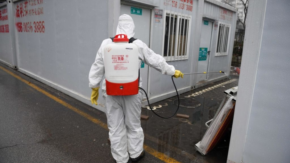 A worker disinfects between containers at the Youan Hospital in Beijing on February 14, 2020. - Youan Hospital is one of twenty hospitals in Beijing treating coronavirus patients. Six health workers have died from the COVID-19 coronavirus in China and more than 1,700 have been infected, health officials said on February 14, underscoring the risks doctors and nurses have taken due to shortages of protective gear. (Photo by GREG BAKER / AFP) (Photo by GREG BAKER/AFP via Getty Images)