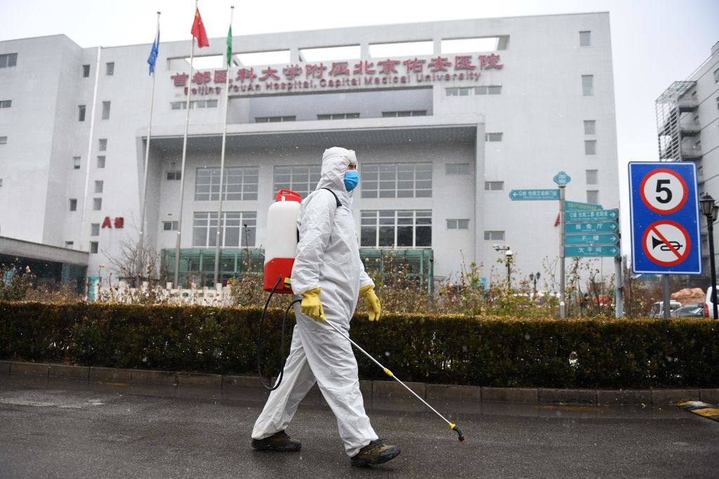 A worker sterilises a path at the Youan Hospital in Beijing on February 14, 2020. - Youan Hospital is one of twenty hospitals in Beijing treating coronavirus patients. Six health workers have died from the COVID-19 coronavirus in China and more than 1,700 have been infected, health officials said on February 14, underscoring the risks doctors and nurses have taken due to shortages of protective gear. (Photo by GREG BAKER / AFP) (Photo by GREG BAKER/AFP via Getty Images)