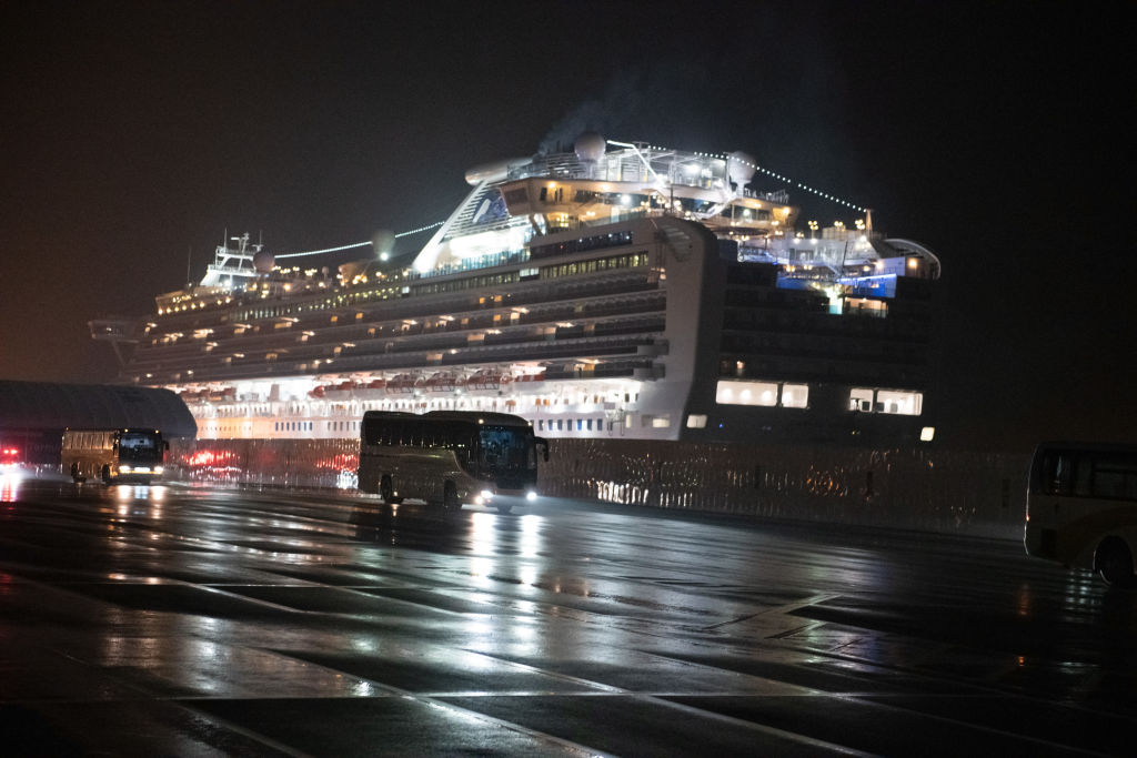 YOKOHAMA, JAPAN - FEBRUARY 17: Buses carry American citizens from the quarantined Diamond Princess cruise ship at Daikoku Pier to be repatriated to the United States, on February 17, 2020 in Yokohama, Japan. The United States has become the first country to offer to repatriate citizens on the Diamond Princess cruise ship while it remains quarantined in Yokohama Port as at least 355 passengers and crew onboard have tested positive for the coronavirus (COVID-19). Including cases onboard the ship, 408 people in Japan have now been diagnosed with COVID-19 making it the worst affected country outside of China. (Photo by Carl Court/Getty Images)