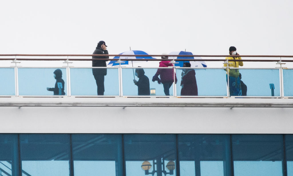Passengers of the Diamond Princess cruise ship, who are quarantined due to fear of the new COVID-19 coronavirus, walk on the deck of the ferry docked at the Daikaku Pier Cruise Terminal in Yokohama port on February 16, 2020. - Americans began leaving a quarantined cruise ship off Japan on the night between February 16 and February 17, 2020 to board chartered flights home as the number of new coronavirus cases diagnosed on the vessel jumped to 355. (Photo by Behrouz MEHRI / AFP) (Photo by BEHROUZ MEHRI/AFP via Getty Images)