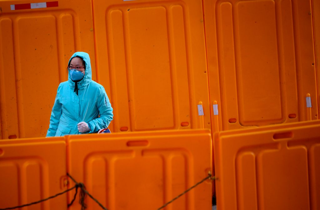 A woman wearing a protective facemask walks past construction barriers along a street in Shanghai on February 19, 2020. - The death toll from China's new coronavirus epidemic jumped past 2,000 on February 19 after 136 more people died, with the number of new cases falling for a second straight day, according to the National Health Commission. (Photo by NOEL CELIS / AFP) (Photo by NOEL CELIS/AFP via Getty Images)