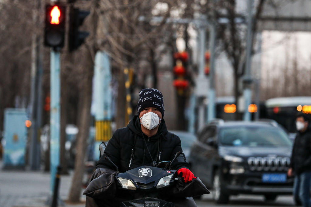 BEIJING, CHINA - FEBRUARY 19: A Chinese man wears a protective mask as he rides on the street on February 19, 2020 in Beijing, China. AsThe number of cases of a deadly new coronavirus has risen to more than 74,000 in mainland China, and as of today, 2,009 patients have died. (Photo by Lintao Zhang/Getty Images)