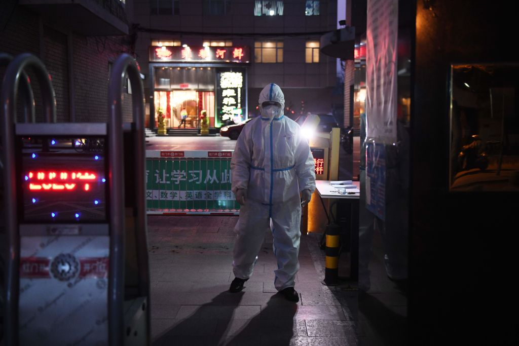 TOPSHOT - A security guard wears protective clothing as a preventive measure against the COVID-19 coronavirus as he stands at the entrance of a restaurant in Beijing on February 25, 2020. - China on February 25 reported another 71 deaths from the novel coronavirus, the lowest daily number of fatalities in over two weeks, which raised the toll to 2,663. (Photo by GREG BAKER / AFP) (Photo by GREG BAKER/AFP via Getty Images)