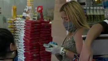 Venezolanos que estarán en cuarentena compran alimentos