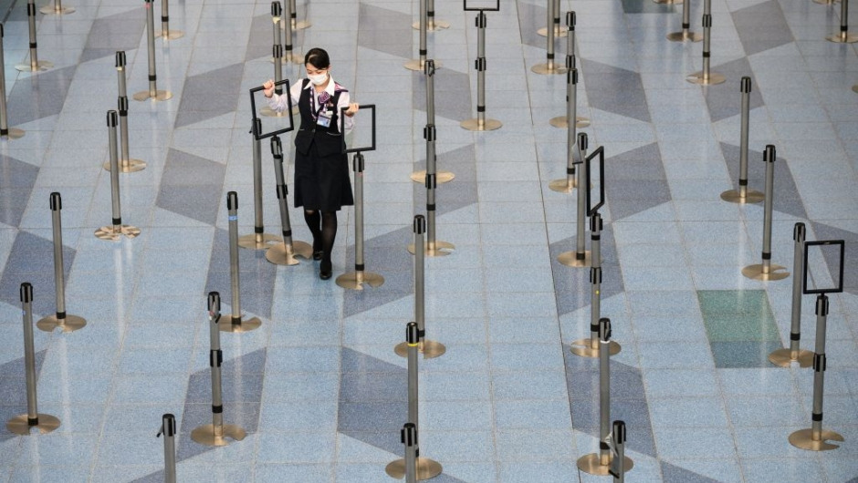 TOPSHOT - A facemask-clad airline employee works at the departure hall of Tokyo's Haneda Airport on March 10, 2020. - The death toll from the COVID-19 illness caused by the novel coronavirus neared 4,000, with more than 110,000 cases recorded in over 100 countries since the epidemic erupted in December in Wuhan, China. It has disrupted global travel, and cancelled conferences and sporting events. (Photo by Philip FONG / AFP) (Photo by PHILIP FONG/AFP via Getty Images)