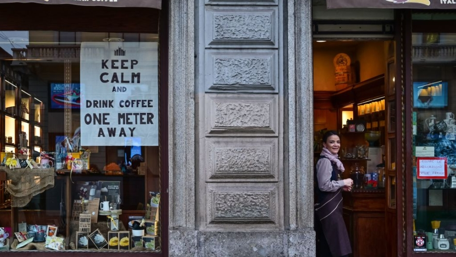 TOPSHOT - A waitress looks on by a sign advising clients to keep distance on a cafe's window on March 10, 2020 in downtown Milan. - Italy imposed unprecedented national restrictions on its 60 million people on March 10, 2020 to control the deadly coronavirus, as China signalled major progress in its own battle against the global epidemic. (Photo by MIGUEL MEDINA / AFP) (Photo by MIGUEL MEDINA/AFP via Getty Images)